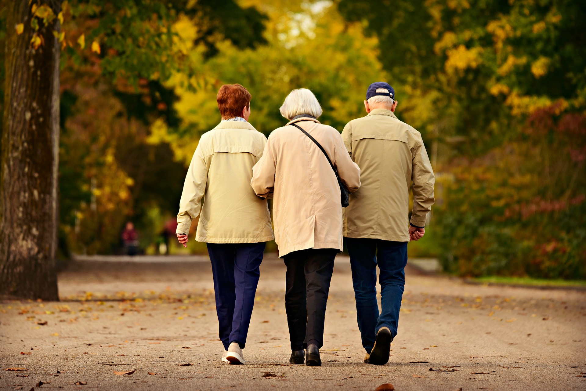 older couple walking arm in arm with adult daughter