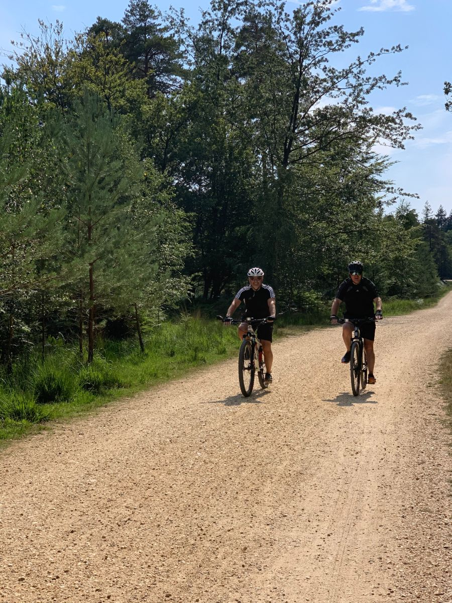two people cycling through forest