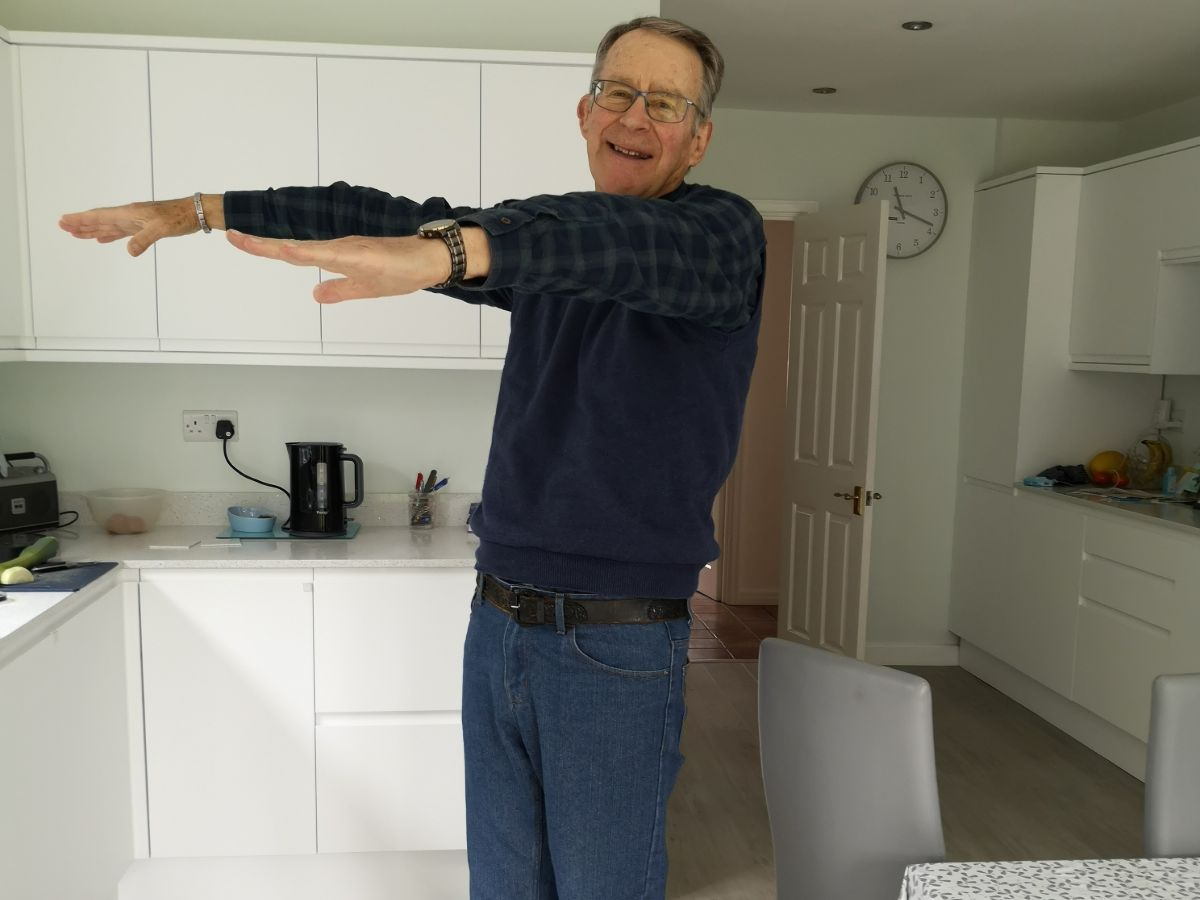 older man doing workout in kitchen