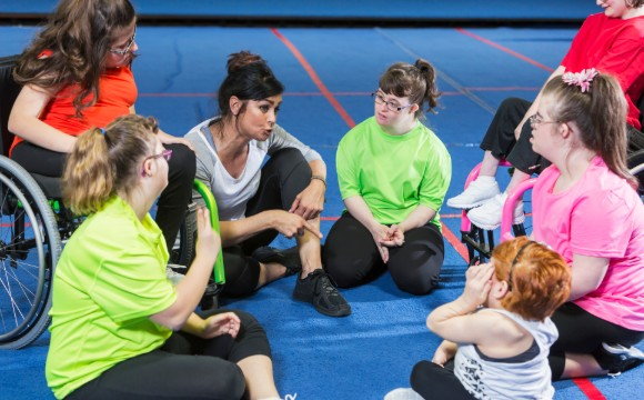 Inclusive fitness coach talking to participants
